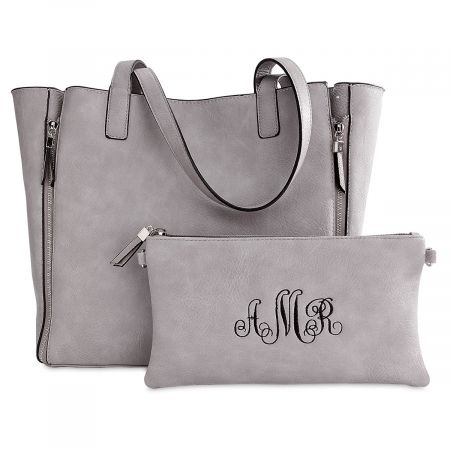 Gray Carry-All Nora Tote Bag with Matching Personalized Crossbody Purse Made with vegan cowhide leather, this bag is two bags in one. The large tote measures 13 L x 5 1/2 W x 12H  with expandable zippers to hold all your stuff. Inside there's a double open wall pocket and a magnetic snap. The bag is embellished with silver hardware. The monogrammed crossbody bag measures 10 1/2L x 1/2W x 6H. You can fill it with your smaller items and use as an organizer inside the large tote, or use it by itself with its detachable crossbody strap. Includes an RFID protected lining to keep your credit cards and passport protected. However, the RFID lining will block cell phone signals. Wipe clean with damp cloth. Specify 3 initials (first, last, middle in this order) for crossbody purse. .