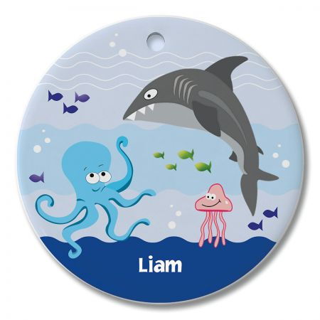 Round Personalized Under the Sea Ceramic Ornament Ahh, the sea. Get your snorkeling gear. but let's wait on the dock until the shark leaves! Still, there's your own name on this small but expressive decor piece. Personalized ornament hangs in a window or pins to a bulletin board. Everyday ceramic ornaments are fun for children, teens, and adults. This round ornament: Measures 2-3/4  in diameter Is printed and personalized on one side Includes ribbon you can attach for hanging Features beautiful custom lettering Wipes clean with a damp cloth Specify 1 line up to 12 characters